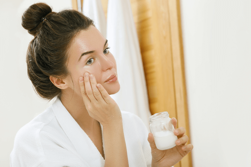 Woman applying coconut oil on her face.