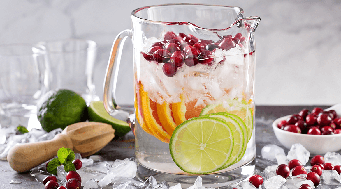 pitcher of water with berries and fruits.