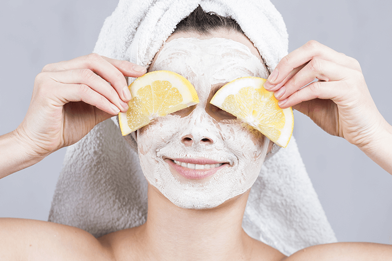 Woman in face mask holding lemon slices.