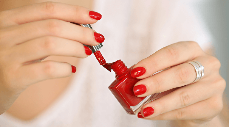 woman painting her fingernails red