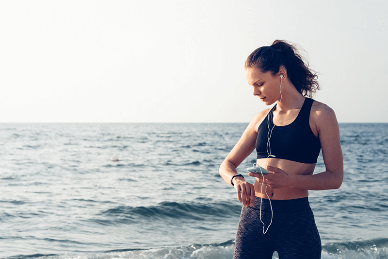 woman checking fitness tracker on beach