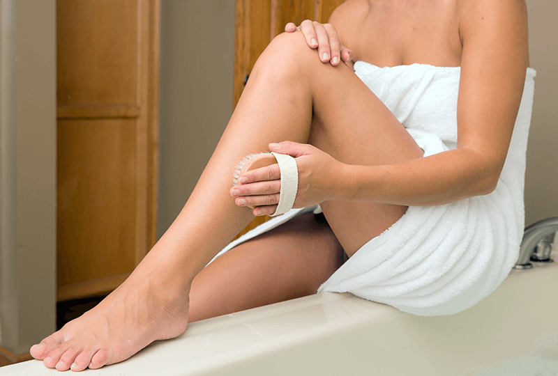 woman dry brushing her leg