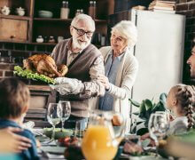 family serving Thanksgiving dinner
