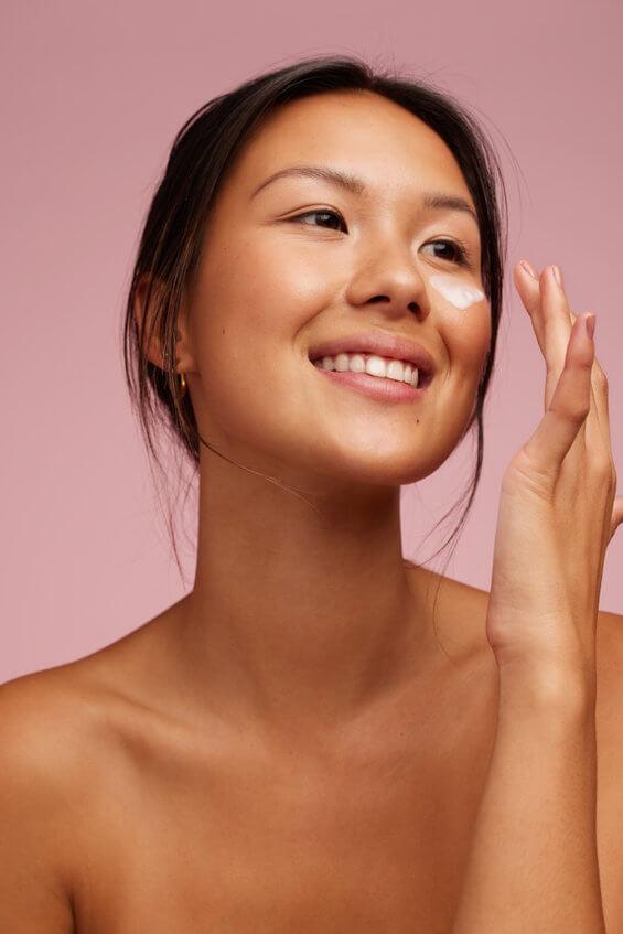 smiling woman applying face serum