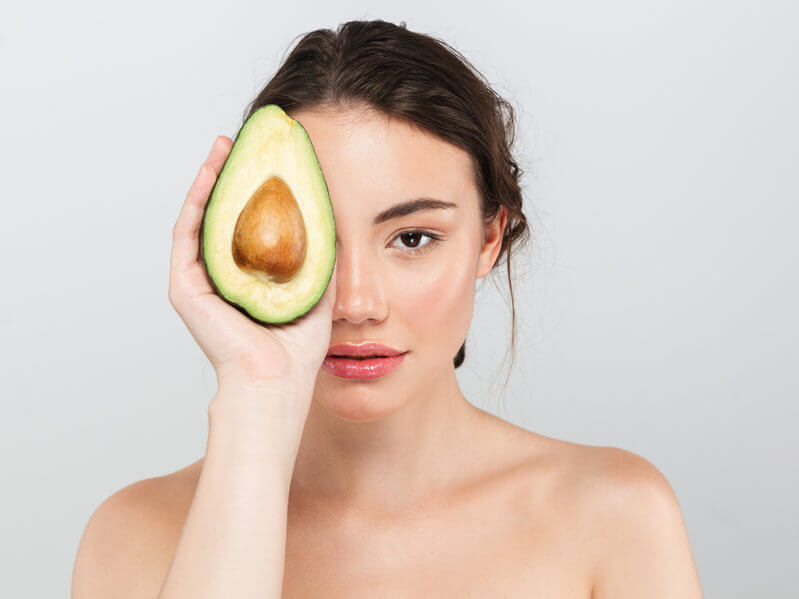 woman with glowing skin holding avocado in front of her eye