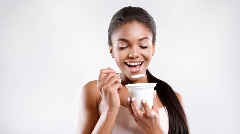 smiling woman eating yogurt
