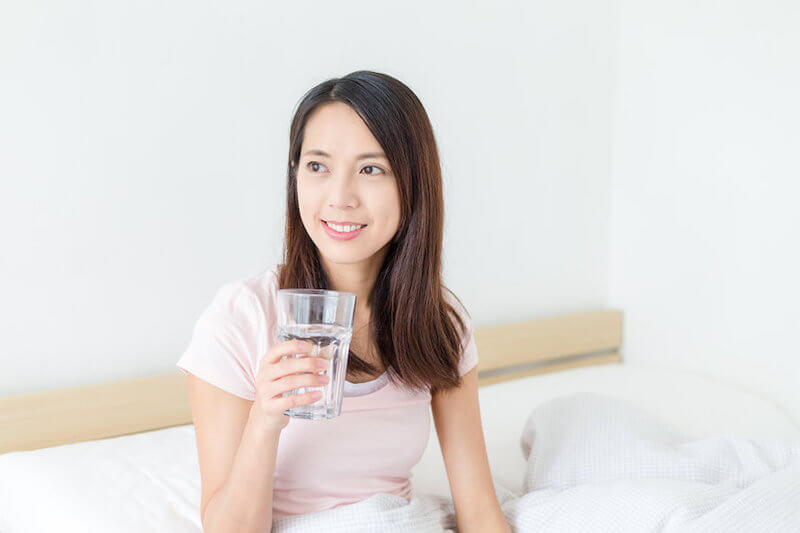 woman smiling while holding glass of water